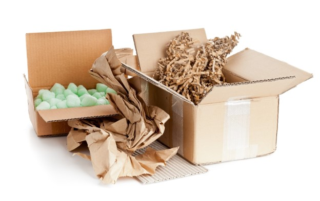 Brown recyclable shipping boxes that are corrugated and filled with biodegradable Kraft paper and loose-fill packing peanuts