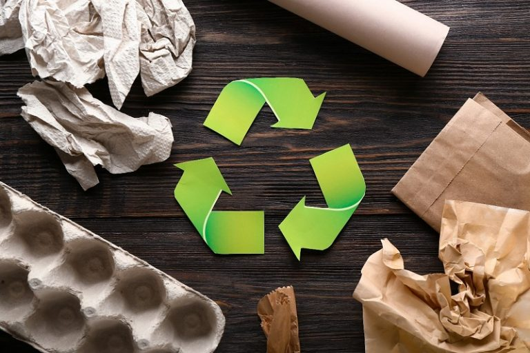 recyclable packaging and shipping materials on a dark brown-colored wooden table with a green recycling symbol in the middle of the picture