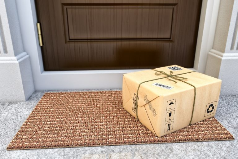 light brown colored kraft paper wrapped around a corrugated shipping box placed on a doormat in front of a brown wooden door